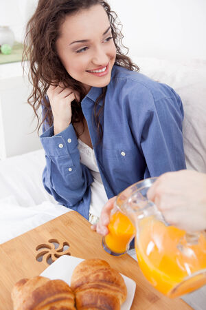 young couple having breakfast and drink orange juice photo