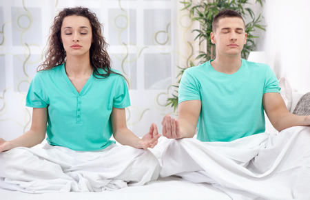 couple in bed together meditating photo