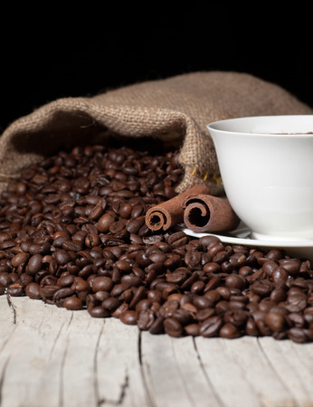 cup of coffee, cinnamon sticks and roasted coffee beans photo