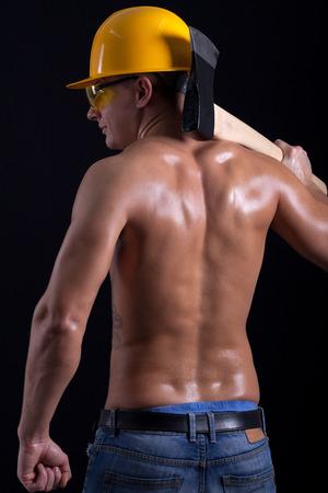 Ņhatchet: young muscular worker holding hatchet Stock Photo