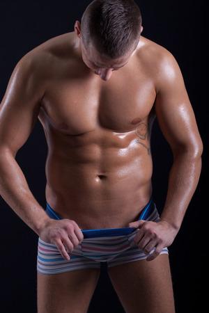 pantalones abajo: muscular hombre mirando hacia abajo en sus pantalones Foto de archivo
