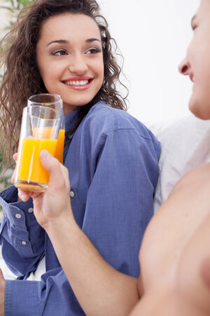 young couple having breakfast in bed toast with orange juice photo