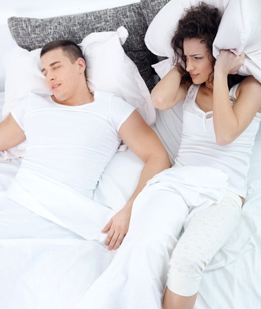 Young couple in bed woman trying to sleep while a man is snoring photo