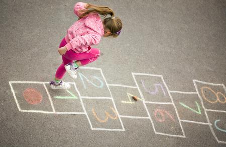 preschool: beautiful litlle girl on the hopscotch