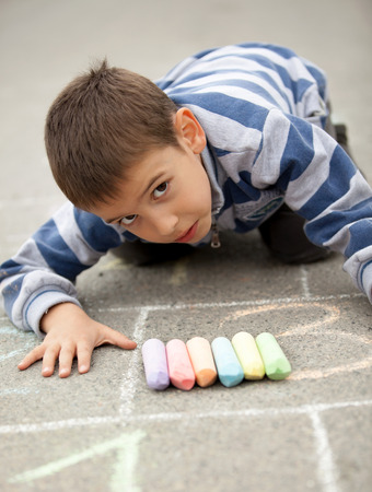 Cute little boy drawing with chalk outdoors  photo