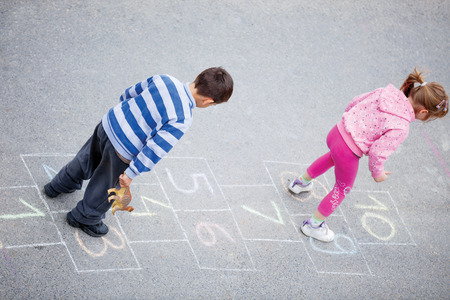 beautiful litlle boy and girl on the hopscotch
