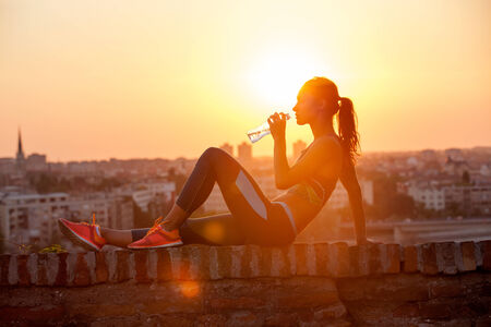 hot drink: silhouette of girl drinking water outdoor