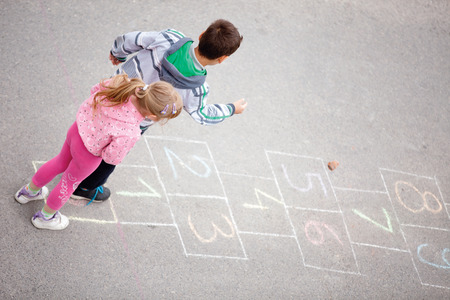 beautiful litlle boy and girl on the hopscotch photo