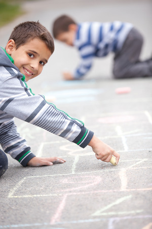 little boy drawing with chalk outdoors photo