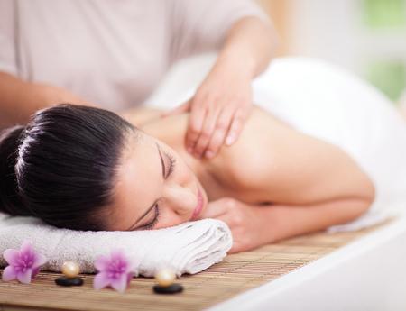 Belle femme ayant un massage bien-être de revenir à un salon de spa