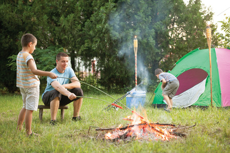 happynes: family on a camping trip, the father and son baking sausage Stock Photo