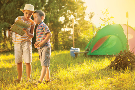 children on a camping trip learning how to read and use a map Stock Photo