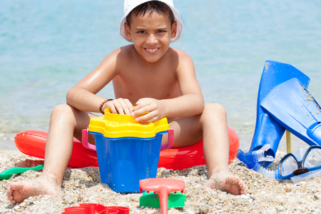 little boy enjoying on the beach playing in the sand photo