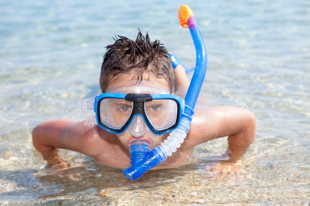 scuba goggles: boy with flippers lying in the sea