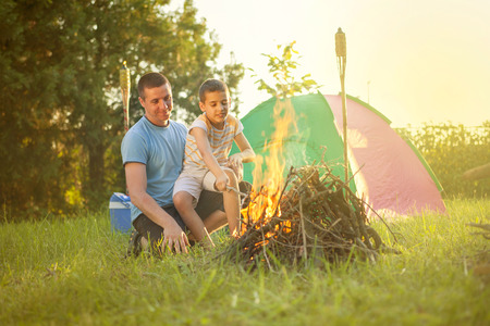 happynes:  happy family near campfire roasting sausages Stock Photo