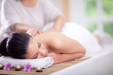 Beautiful woman having a wellness back massage at spa salon  Foto de archivo