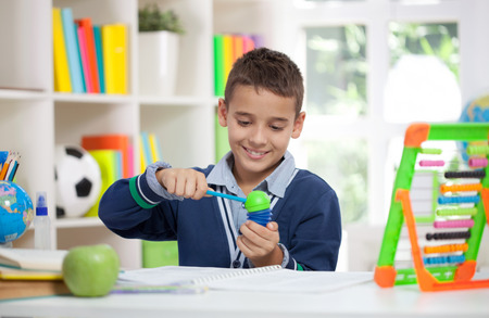 grade schooler: smiling schoolboy siting at the desk in home and sharp pencil Stock Photo