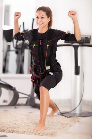 women body: fit woman exercise on electro muscular machine
