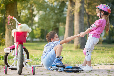 girl in park, helps boy with roller skates to stand up