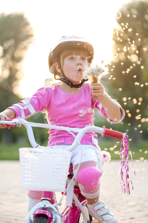 blond little girl on her bike blowing a dandelion  photo