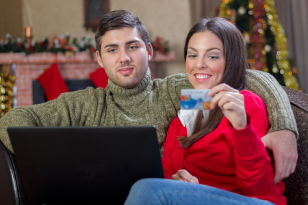 Couple Using Credit Card to E-Shop on christmas night photo