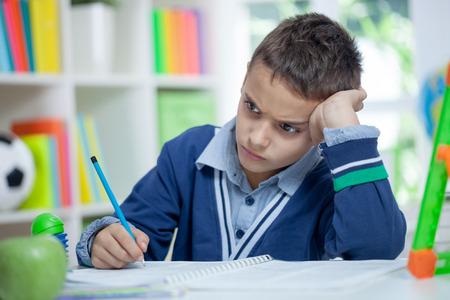 Un garçon triste et fatigué assis à son bureau