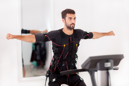 fit man exercise on  electro muscular stimulation machine