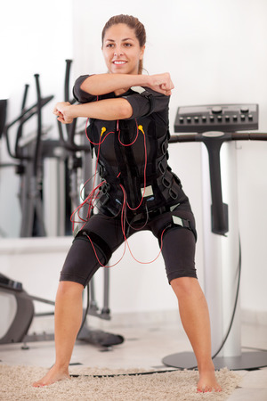 young fit woman exercise on electro muscular stimulation machine