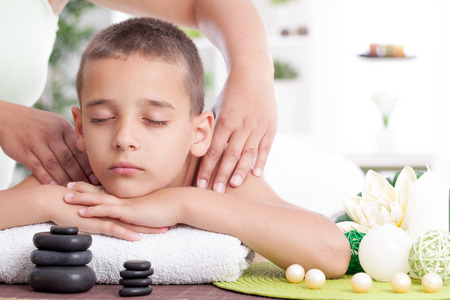 litle:  young boy  relaxing in spa. stone massage.
