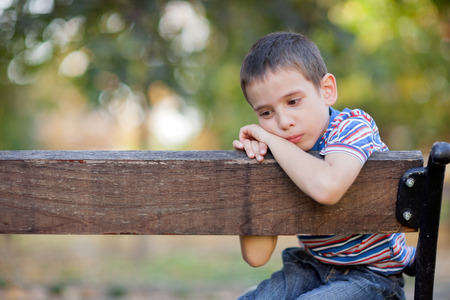boy sitting: lonely young orphan in park crying