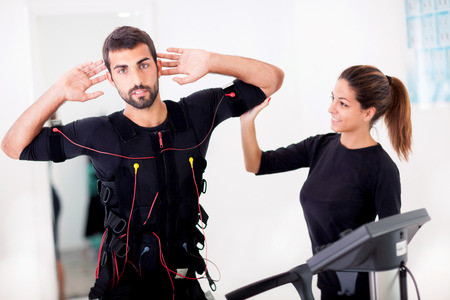 electrical: man exercise trunk-twist and bending with curled back, with ems stimulation