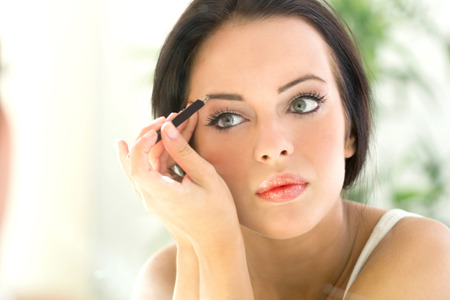 beautiful young woman applying Make-up