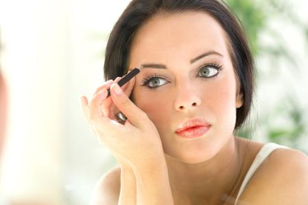 mujer maquillandose: bella joven de aplicar maquillaje