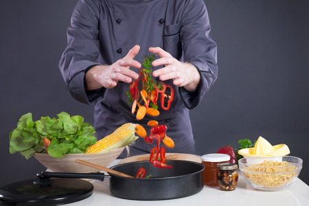 Chef throws various vegetables in a pan photo