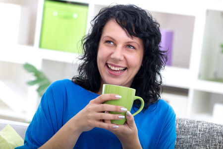 tenager: woman sitting at her home drinking coffe, smiling. Stock Photo
