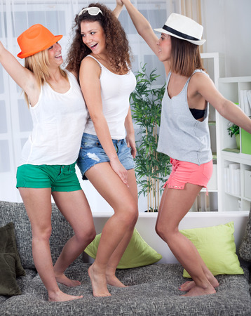 dancing woman: Three funny young girls having party at home