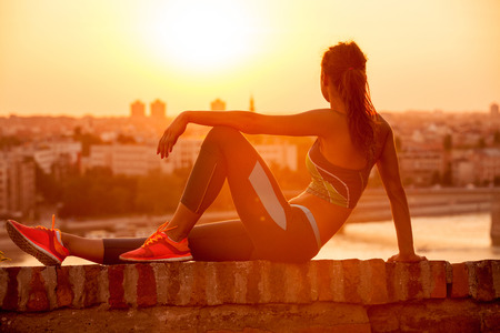 Sports woman resting and enjoying in the sunset after a hard workout