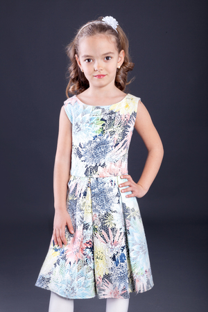 little girl in luxurious dress on gray background