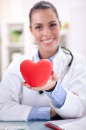 healthcare and medicine concept - smiling female doctor with heart and stethoscope photo