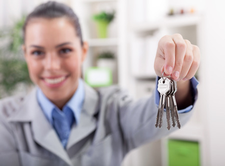 accommodation broker: young female agent for the sale of apartments delivered the keys Stock Photo