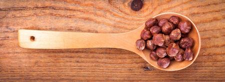 nit: Hazelnuts in wooden spoon,on wooden background