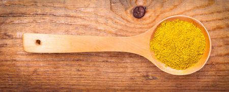 trituration: curry powder spices on spoons,on wooden background
