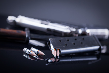 magazine knife, pen in the form of bullet and blurred gun in the background Stock Photo
