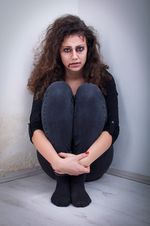 raped: domestic and rape violence,beaten and raped sitting in the corner Stock Photo