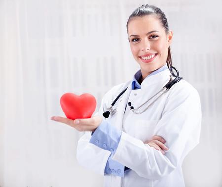 buena salud: cuidado de la salud y el concepto de la medicina - sonriente mujer m�dico con el coraz�n y el estetoscopio Foto de archivo