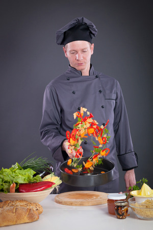studio happy overall: male chef tossing vegetables from wok in kitchen