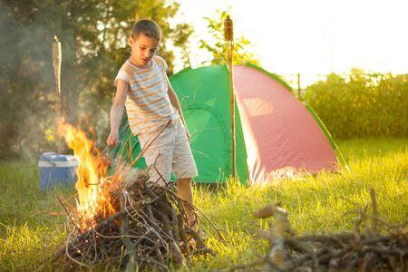 happynes: young  happy boy near campfire