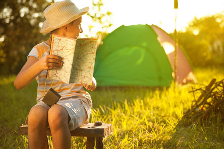 verano: Campamento en la carpa - muchacho joven en una acampada
