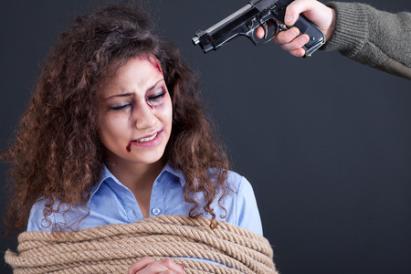 pious: terrorists holding a gun to a womans head Stock Photo