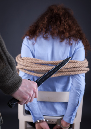 woman turned back tied with a rope, waiting terrible fate of the executioner, who holds a knife in his hand